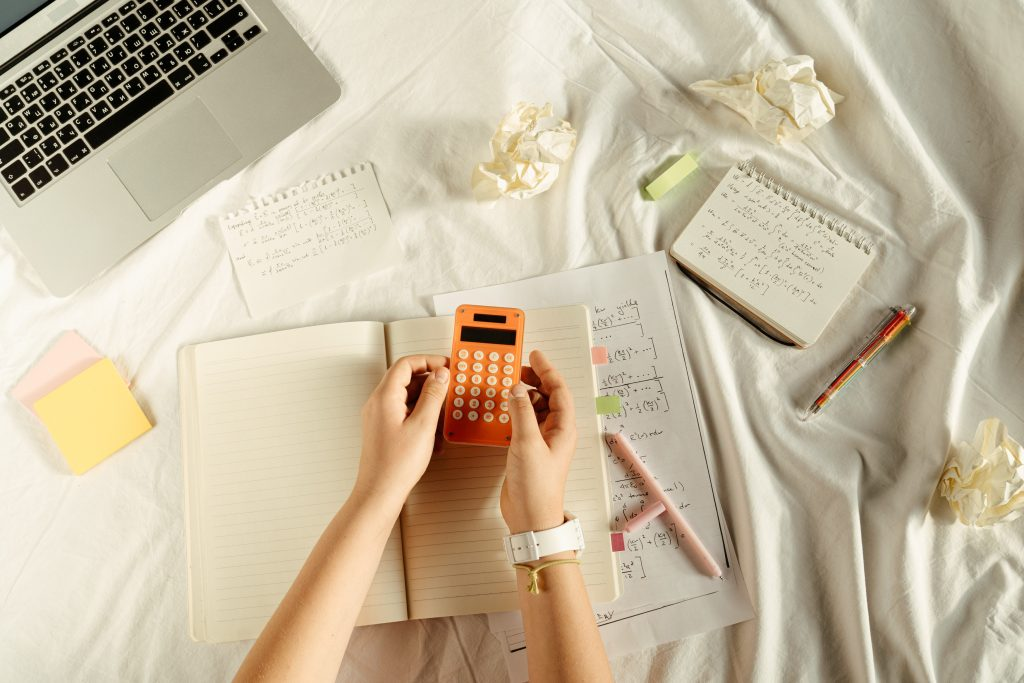Pairs of hands holding calculator above stack of notebooks on desk.